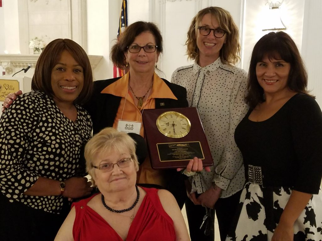LIHS Deputy Director Marian D. Reid, LIHS Gala Committee Chair/Board Secretary Carol Germann (seated); LIHS Executive Director emeritus Michelle Santantonio (holding plaque); LIHS Financial Manager Jill Garrick; LIHS Outreach coordinator Ana Poppe (left to right). Photo by Kimberly Wilder.